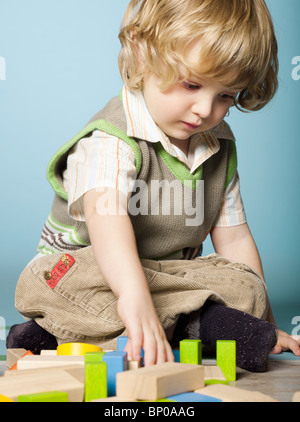 Little boy playing with wooden blocks - Stock Photo