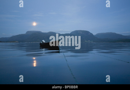 Wooden boat on calm sea at night - Stock Photo