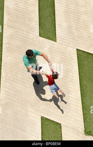 Father swinging son in the air - Stock Photo