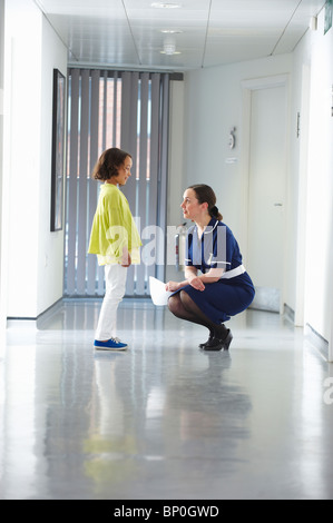 Nurse talking to child in corridor - Stock Photo