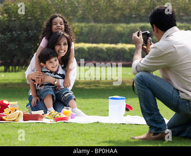 Man taking a photograph of his family - Stock Photo