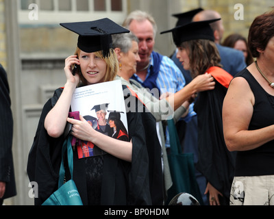 A University of Sussex graduate phones a friend before heading inside Brighton Dome for her graduation ceremony - Stock Photo
