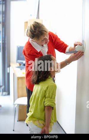 Doctor measuring height of young girl - Stock Photo