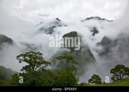 Peru, In the early morning, low mist and clouds rise from the steep-sided valleys surrounding the Inca ruins at - Stock Photo