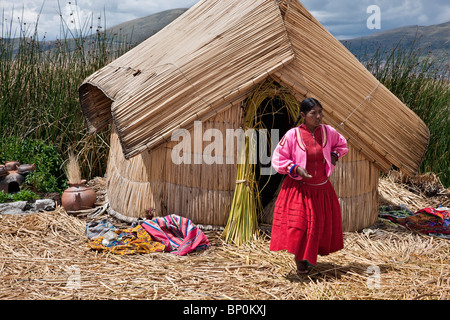 Peru, A girl from Uros outside her reed home on one of the unique floating islands of Lake Titicaca. - Stock Photo