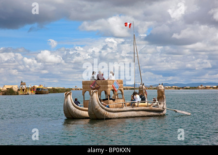Peru, A large reed boat is rowed down the main channel between the unique floating islands of Uros on Lake Titicaca. - Stock Photo