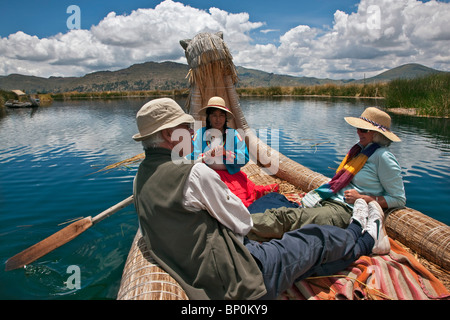 Peru, Tourists being rowed in a traditional reed boat around the unique floating islands of Uros on Lake Titicaca. - Stock Photo