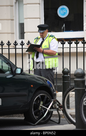 A Traffic warden issues a ticket before  the removal of an illegally parked car from a disabled bay in Brighton - Stock Photo