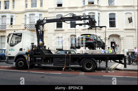 A Traffic warden supervises the removal of an illegally parked car from a disabled bay in Brighton - Stock Photo