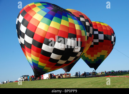 Three colorful hot air balloons preparing for flight. - Stock Photo