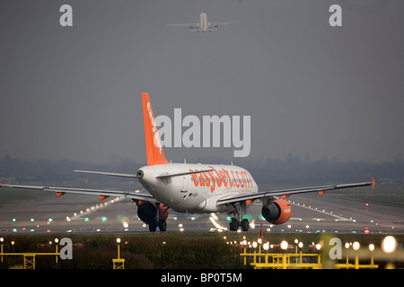 A EasyJet aircraft  taxis onto the runway at Gatwick Airport. Picture by James Boardman - Stock Photo
