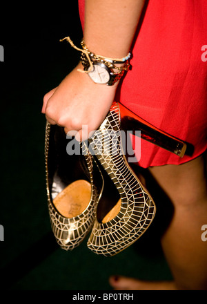 Girl at a party carrying her shoes - Stock Photo