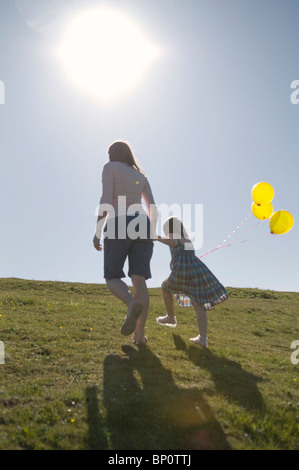 Mother and child with balloons on hill - Stock Photo