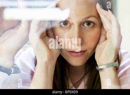 Woman looks thru glass - Stock Photo