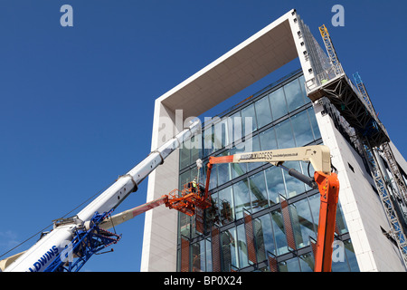 construction workers working at height to install cladding on Southern Operational Command Unit Southampton - Stock Photo