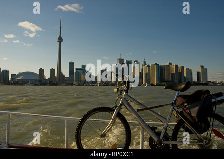 City of Toronto skyline from island ferry with bicycle in foreground. - Stock Photo