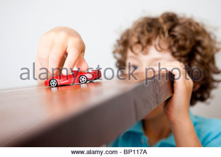 Boy playing with small red car - Stock Photo