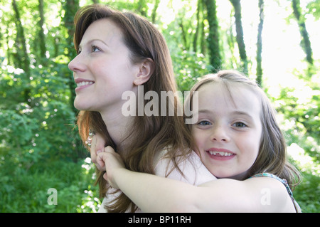 Woman gives child piggy back - Stock Photo