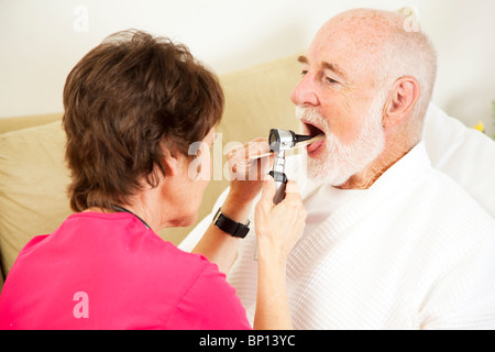 Home health nurse checks a patient's throat with an otoscope.  - Stock Photo