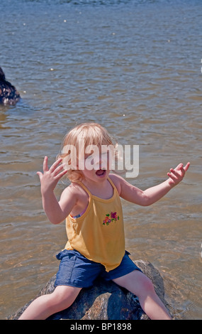 Caucasian girl is thoroughly enjoying a summer moment as she's sitting on a rock in a lake and singing her little - Stock Photo