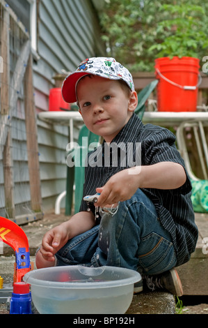 This cute 6 year old Caucasian boy with freckles & wearing a cap and blue jeans is playing outside with cars in - Stock Photo