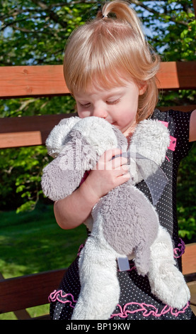 This precious shot image shows a Caucasian 2 year old girl kissing her favorite stuffed animal, a white and gray - Stock Photo