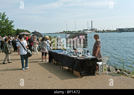 Tourists at Langelinie in Copenhagen viewing a TV screen showing The Little Mermaid on display in Shanghai China - Stock Photo