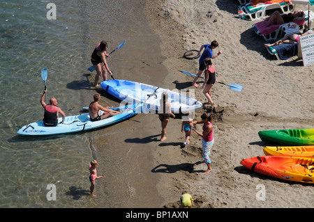 Holidaymakers with kayaks on the beach at Collioure a resort in southern France - Stock Photo