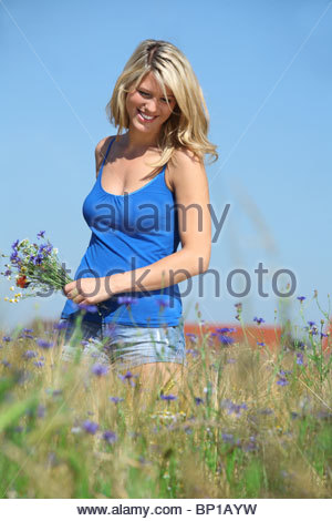 blond woman walking through fields picking wild flowers - Stock Photo