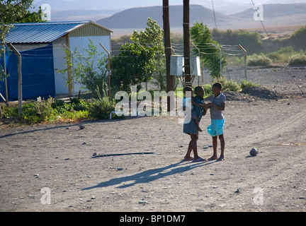 Two young girls and infant on gravel road in Aus, Namibia - Stock Photo