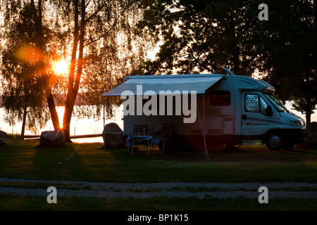 A camper trailer at a lake in sunset. - Stock Photo
