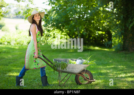 Young woman pushing wheelbarrow - Stock Photo