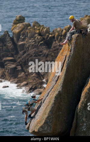 Climbers on rocks on the coast of Gwennap Head in Cornwall. - Stock Photo