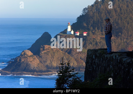 Oregon, United States Of America; A Man Standing On The Edge Of A Cliff Overlooking Pacific Ocean Near Heceta Head - Stock Photo