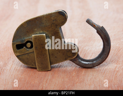Old brass padlock on wooden background - Stock Photo