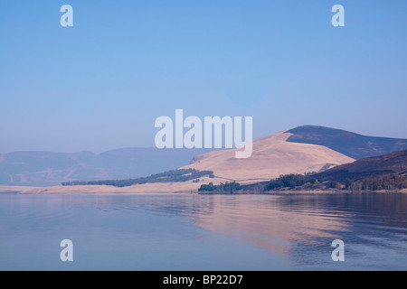 Distant hills reflected in the Midmar dam on a cloudless winter day. Midlands, KwaZulu Natal, South Africa. - Stock Photo