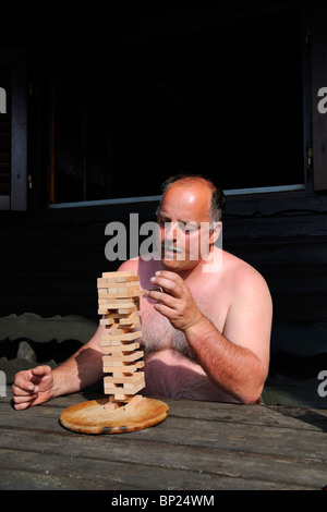 Mature Man playing a tricky board game. - Stock Photo