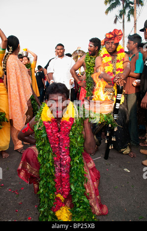 Hindu pilgrim in trance carrying a pot of fire during Thaipusam Festival at Batu Caves in Kuala Lumpur - Stock Photo