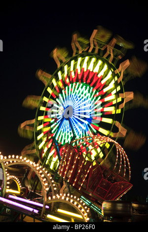 Amusement Rides with Movement Blur in the evening at the Kentucky State Fair Midway Louisville Kentucky - Stock Photo