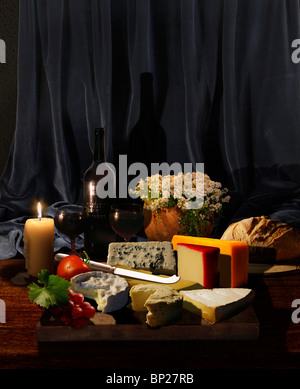 board of cheeses with herbs, fruits, vegetables, wine, bread and flowers in candle candle - Stock Photo