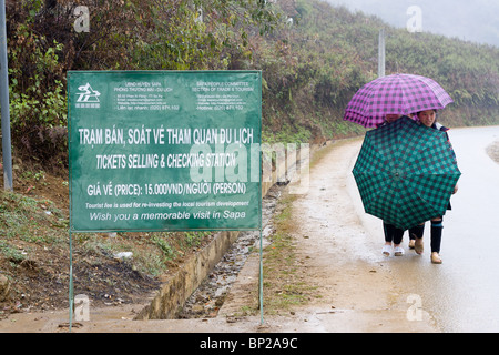 two black Hmong girls with two umbrellas try to stay dry while walking down the road. - Stock Photo