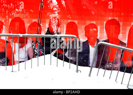 Red poster showing a group of men and women with no faces, set behind a fence covered in snow, New York City, USA. - Stock Photo