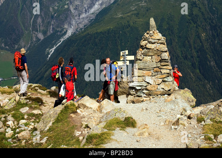 Walkers arriving at a cairn in the Alps on the Route du Mont Blanc, above Chamonix - Stock Photo