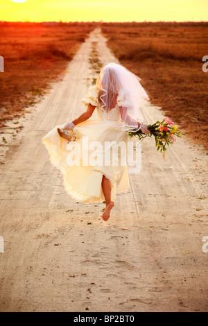 Runaway bride down dirt road - Stock Photo