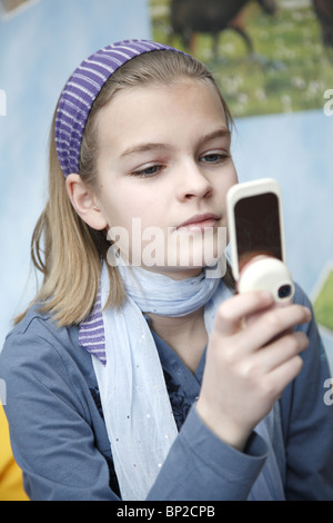 An eleven-year-old girl playing with her mobile phone, Hamburg, Germany - Stock Photo