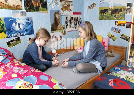 Two sisters playing together in their room - Stock Photo