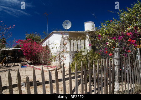 Side view of a modest house with a TV satellite dish on the roof in Corral del Risco, a small village in Nayarit, - Stock Photo