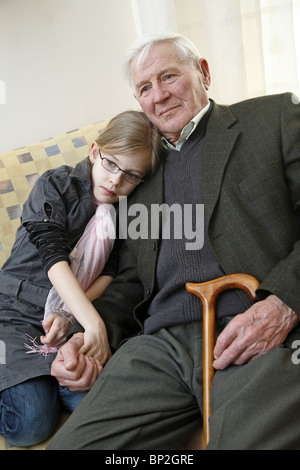Granddaughter cuddling up to her grandfather - Stock Photo