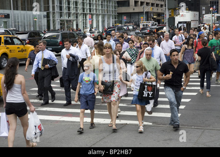 Crowds of people are always crossing 42nd Street by Bryant Park in New York City. - Stock Photo