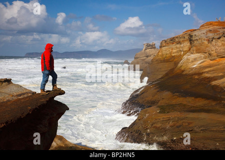 Pacific City, Oregon, United States Of America; A Man Standing On The Edge Of A Cliff Along The Coast At Cape Kiwanda - Stock Photo
